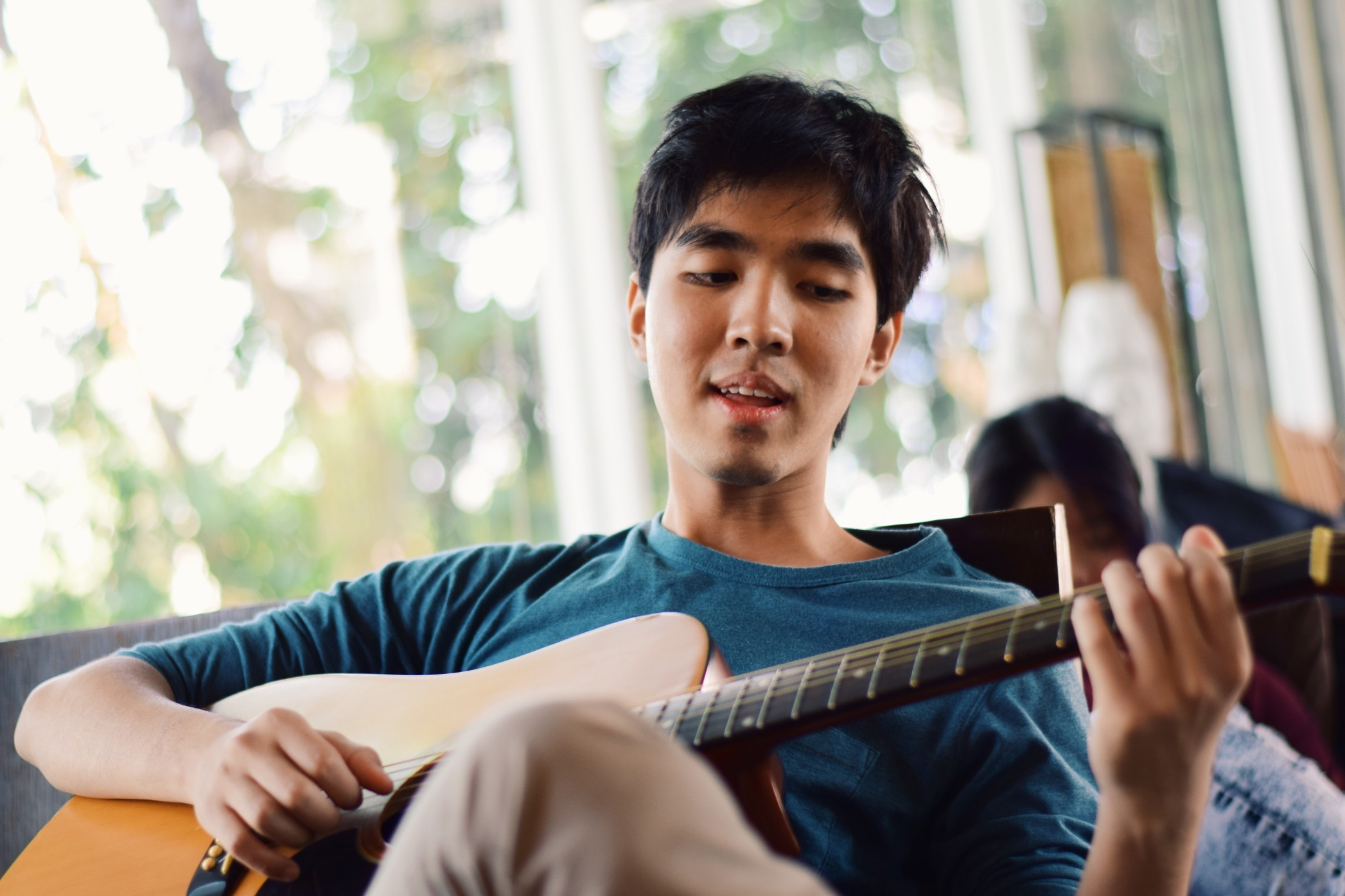 Young man playing the guitar inside