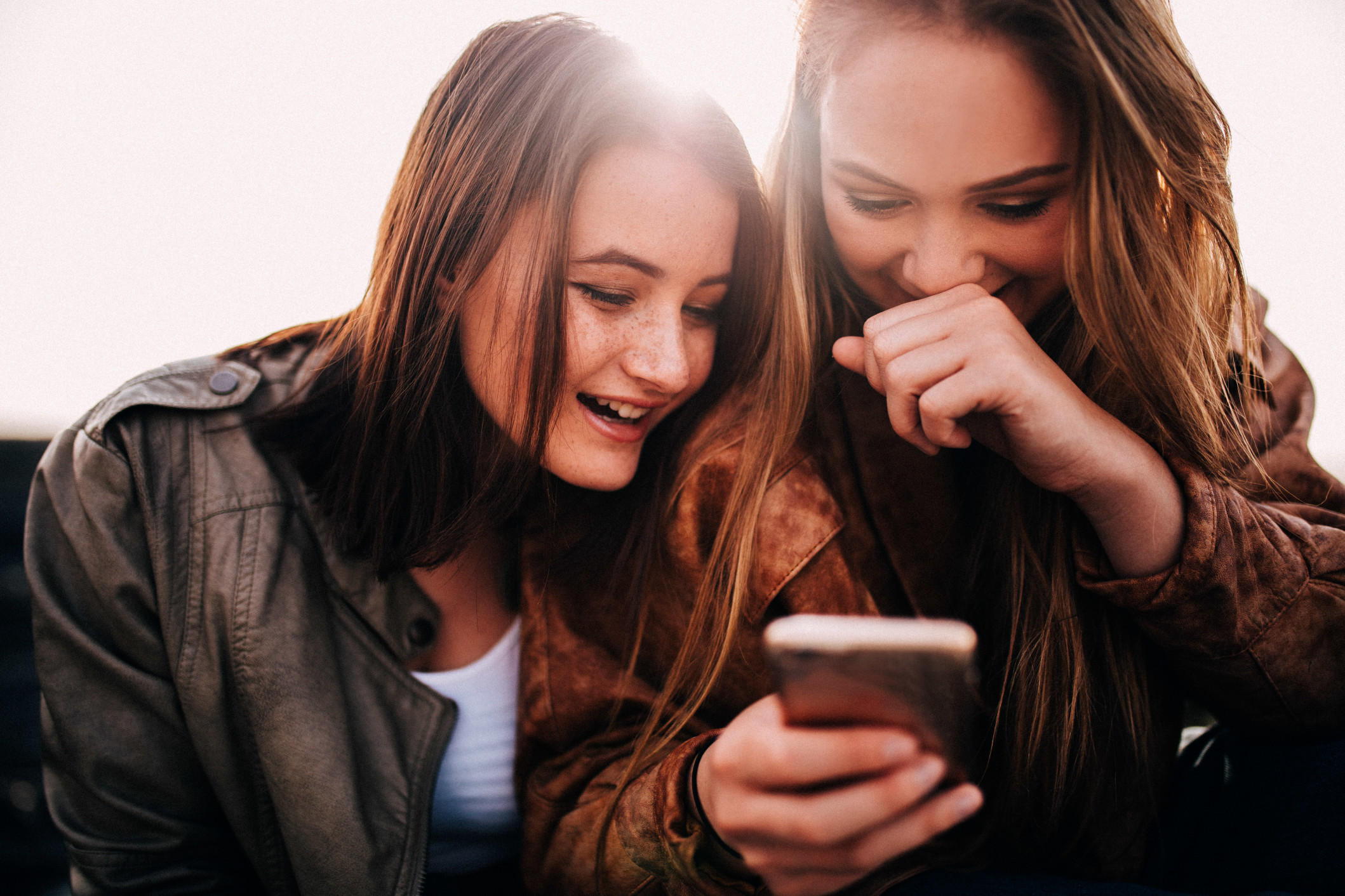 Teenage girls looking at funny photos on smartphone and laughing t20 g8 VN Kb