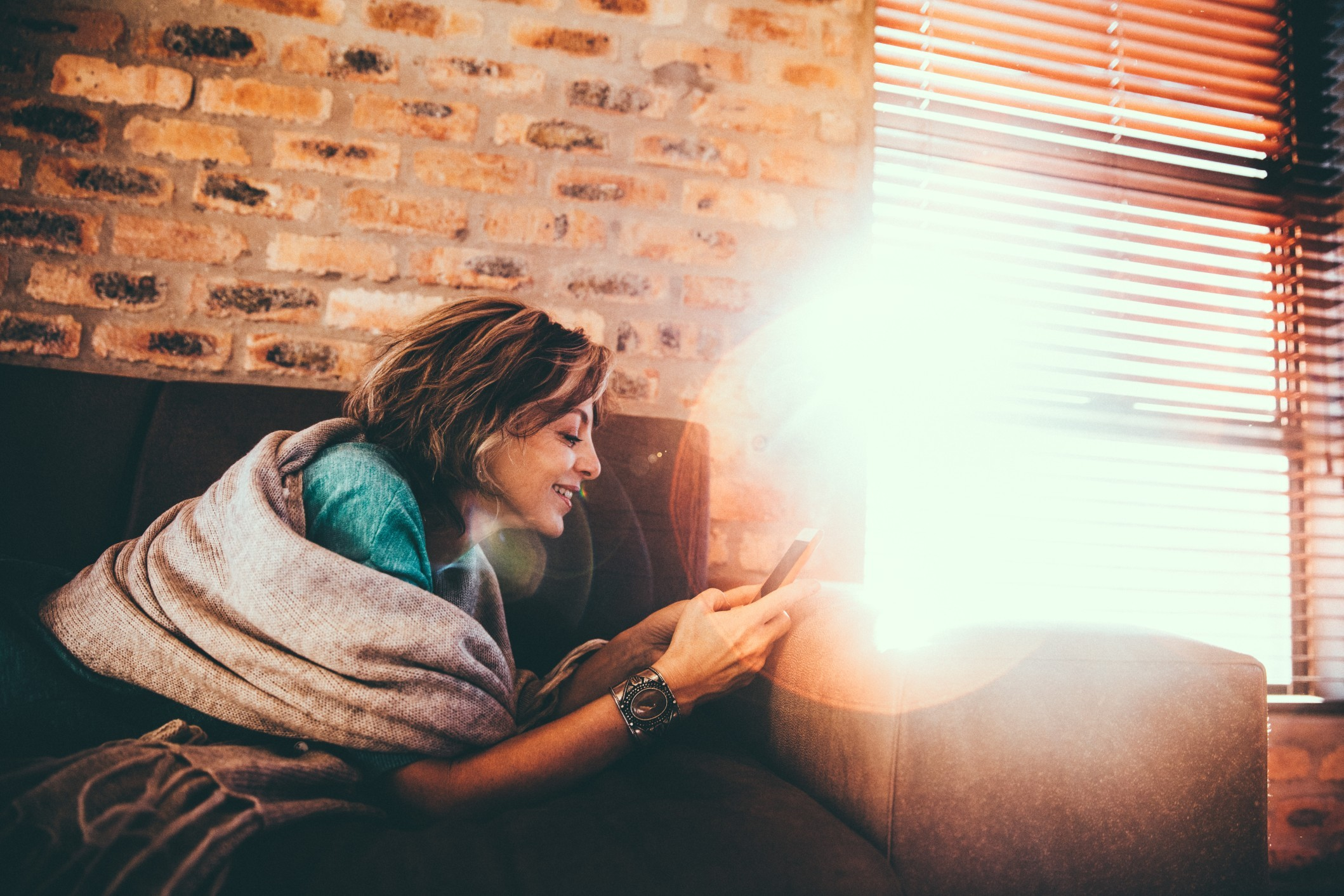 Women using mobile phone on couch at home with sun flare in background t20 Rw6o2w